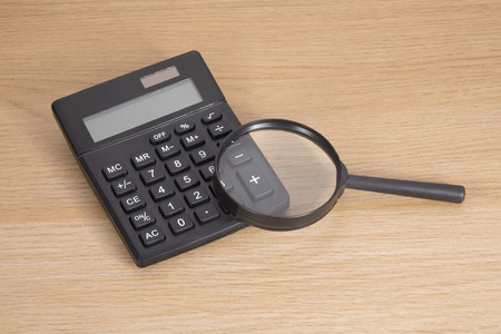 High angle view of calculator with magnifying glass on wooden table Фото со стока