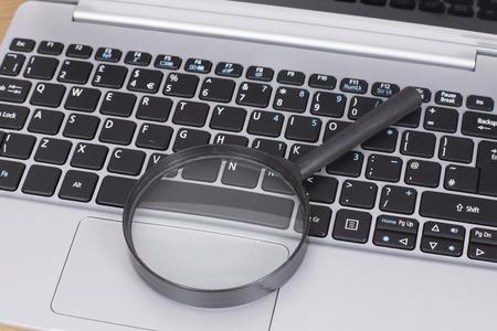 온라인 검색 또는 비즈니스 분석의 개념에서 랩톱 컴퓨터 키보드에 작은 라운드 돋보기