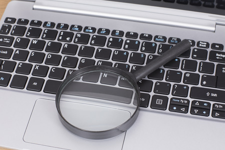 Small round magnifying glass on a laptop computer keyboard in a concept of online search or business analysis Фото со стока
