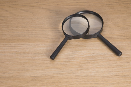 crime solving: Two magnifying glasses lying on wooden table