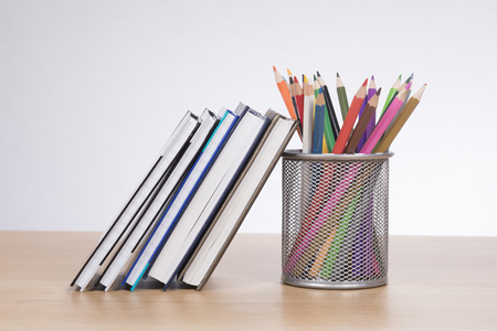 Colored pencil crayons in a mesh container with textbooks and journals for school standing together on a wooden desk