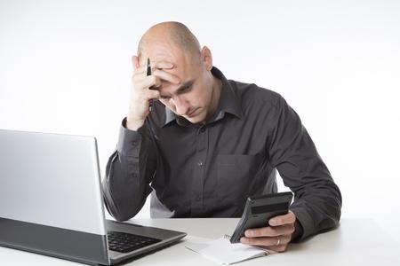 사업가 또는 계산기 그의 손으로 계산기를 들고 그의 책상에서 일하고 회계사는 자신의 컴퓨터와 함께 손으로 쓴 메모를 조심스럽게 훔쳐 본다.