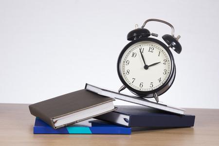 slantwise: Alarm clock standing slantwise on pile of books against plain background
