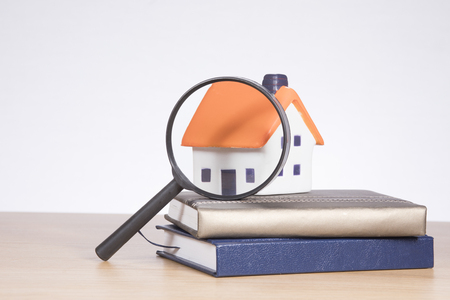 モデル住宅と不動産市場研究テーマ コンセプトの白のコピー スペース付きの拡大鏡の下で木材の机の上の銀行の書籍のスタック。