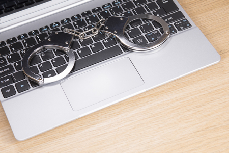 restraints: Handcuffs lying on an open laptop computer keyboard in a concept of online fraud or crime, identity theft and hacking Stock Photo