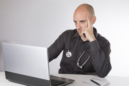 Doctor with a stethoscope around his neck sitting working at his laptop computer resting his chin on his hand with a serious thoughtful expression Фото со стока