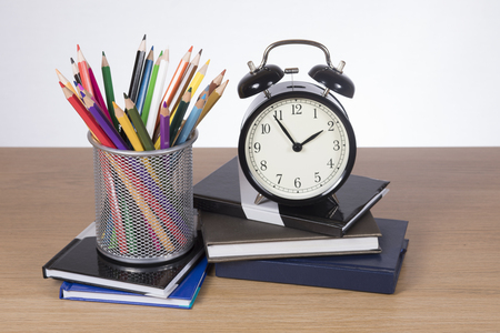 School books, pencil crayons and an alarm clock set to just before two signalling the end of the lunch break and return to classes or home time