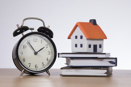 insurance themes: A stack of bank books with a model house and ticking alarm clock on a timber desk with white copy space in a mortgage, finance, insurance themed concept.