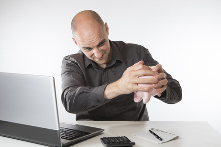 그는 노트북 컴퓨터에서 자신의 계좌로 작업하면서 거꾸로 들고 있기 때문에 필사적으로 더 많은 돈을 위해 돼지 저금통을 흔들어 움직이고있는 남자
