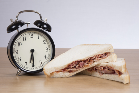 Early morning or late evening bacon sandwich snack on fresh white bread alongside a retro alarm clock with bells and copy space