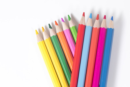 Colorful collection of pencil crayons on white in the colors of the rainbow or spectrum arranged as a V with copy space Stock Photo