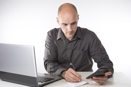 계산기 및 노트북 회계 또는 비즈니스 계획의 개념에서 메모장에 메모를 작성 작업 매력적인 중 년 남자 스톡 콘텐츠