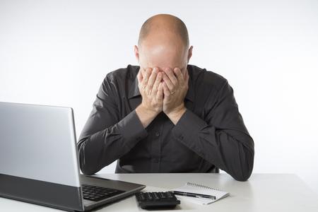 그의 손에 계산기와 그의 머리와 그의 노트북 컴퓨터에 앉아 자신의 계정을 하 고 절망적 인 남자 스톡 콘텐츠