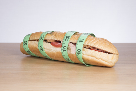 Long baguette sandwich with meat wrapped in measuring tape Stock Photo