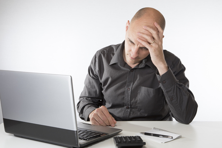 Worried man wondering where he will get the money to balance his accounts as he sits working on his laptop with a calculator and his head on his hands