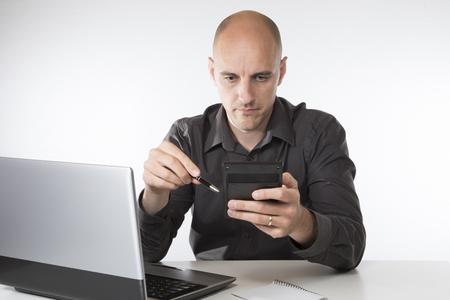 그는 회계, 계획 또는 분석의 개념에서 자신의 컴퓨터에 앉아 수동 계산기 작업 사업가