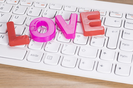 The word love of plastic toy letters over computer keyboard on the desk, close-up high angle concept Stock Photo