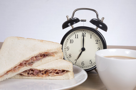 Quick breakfast snack before work with a tasty bacon sandwich on white bread and cup of coffee alongside an alarm clock Stock Photo
