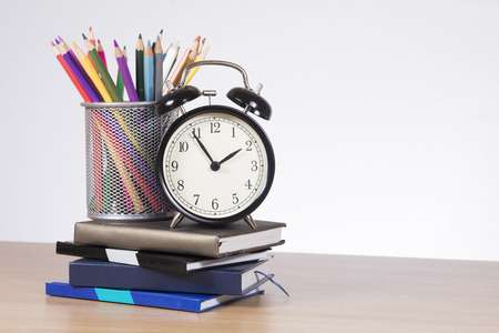 Colored pencils in holder and alarm clock standing on pile of notebooks
