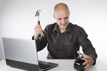 Angry businessman ready to smash an alarm clock to prevent it counting down to a deadline as he sits at his desk working