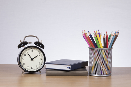 Two notebooks lying between alarm clock and holder with colored pencils against plain background