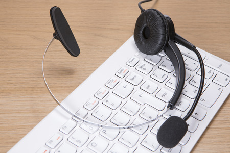 Headset with microphone lying on a white computer keyboard in a business communication and contact concept viewed close up from above