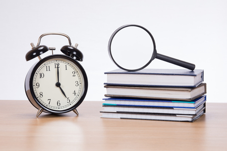 Alarm clock standing by magnifying glass on pile of planners