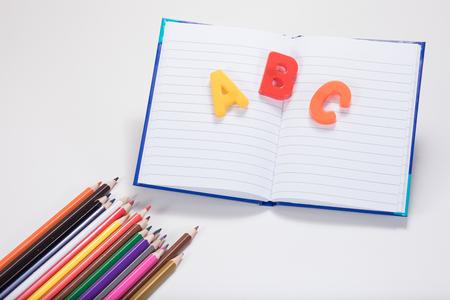 Un concepto de aprendizaje escolar con lápices de colores, libro escolar abierto y letras del alfabeto ABC sobre un fondo blanco liso con espacio de copia. Foto de archivo