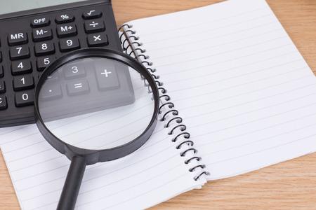 나무 책상에 계산기와 돋보기와 빈 나선형 바인더를 열어