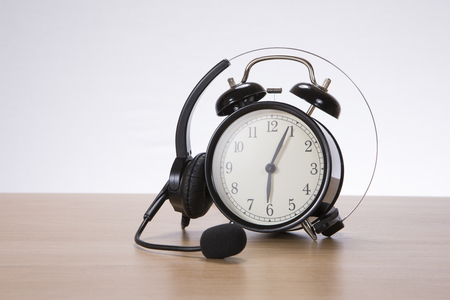 Headset coiled over a retro alarm clock with bells on a wooden table or desk in a conceptual image with copy space