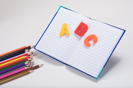 A school learning themed concept with ABC alphabet learning letters, coloured pencils and an open school book with white copy space.