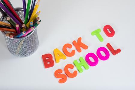 다시 학교로 복사본 공간 평범한 흰색 배경에 색깔 된 연필 바구니 옆에 문자를 학습하는 다채로운 알파벳으로 작성.
