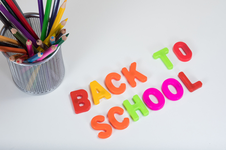 Back to school written with colourful alphabet learning letters next to a basket of coloured pencils on a plain white background with copy space.