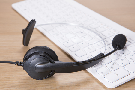 Online business communication concept for client services, telemarketing and live chat with a headset on a computer keyboard Stock Photo
