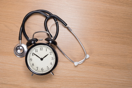 High angle view of stethoscope with alarm clock lying on wooden background