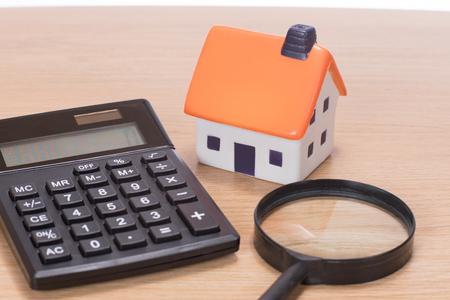 나무 책상에 계산기와 돋보기 가운데 집의 모델 스톡 콘텐츠