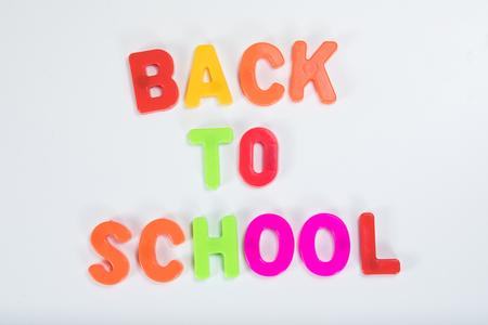 Regreso a la escuela escrita con coloridas letras de aprendizaje del alfabeto sobre un fondo blanco liso con espacio de copia. Foto de archivo