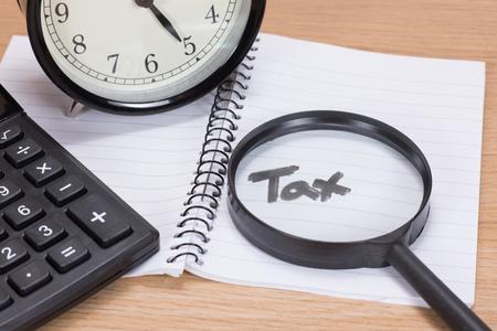 노트북 및 알람 시계와 나무 책상에 계산기에서 필기 텍스트에 돋보기와 세금 마감 개념