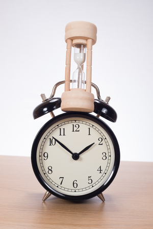 Sandglass standing on alarm clock against plain background