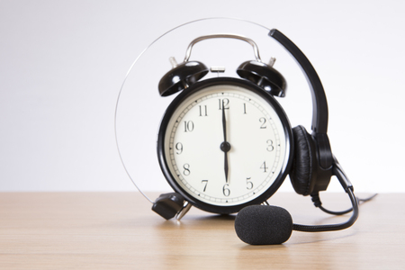 Alarm clock with headset standing on desk against plain background