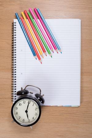 빈 나선형 바인더에 대하여 거짓말 알람 시계와 컬러 연필 스톡 콘텐츠