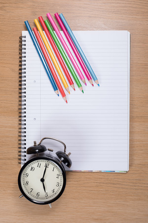 Colored pencils with alarm clock lying against blank spiral binder