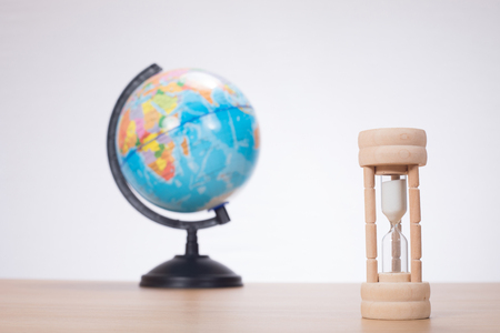 Sandglass with globe standing on desk against plain background Фото со стока