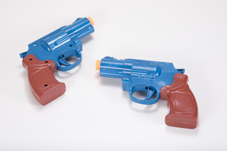 Two opposing plastic toy handguns on a plain white background with copy space.