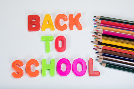 Back to school written with colourful alphabet learning letters beside coloured children pencils on a plain white background with copy space.