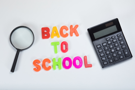 Back to school written in alphabet learning letters alongside a calculator and magnifying glass with white copy space.