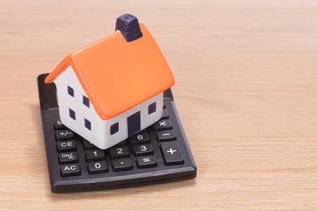 Haus Miniatur stehen auf Rechner vor Holzuntergrund Standard-Bild