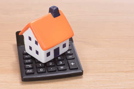House miniature standing on calculator against wooden background