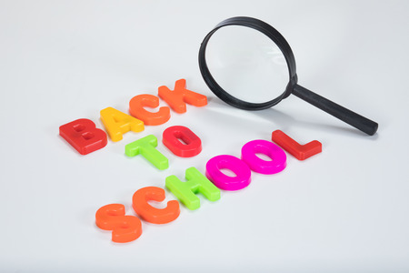 Back to school written in alphabet learning letters alongside a magnifying glass standing on its edge with plain white background and copy space.