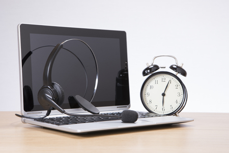 Alarm clock standing by laptop with headset on desk against plain background